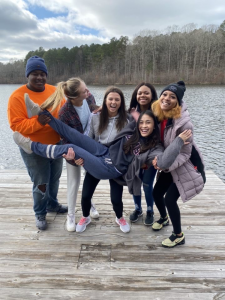 Group of individuals smiling and laughing standing on a dock holding up one person with a body of water in the backdrop